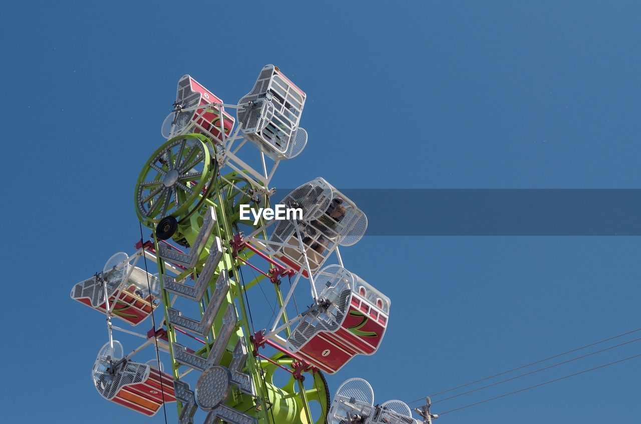 sky, low angle view, nature, no people, blue, clear sky, day, metal, multi colored, sunlight, copy space, outdoors, large group of objects, arts culture and entertainment, amusement park ride, tall - high, spinning, technology, hanging, amusement park, silver colored