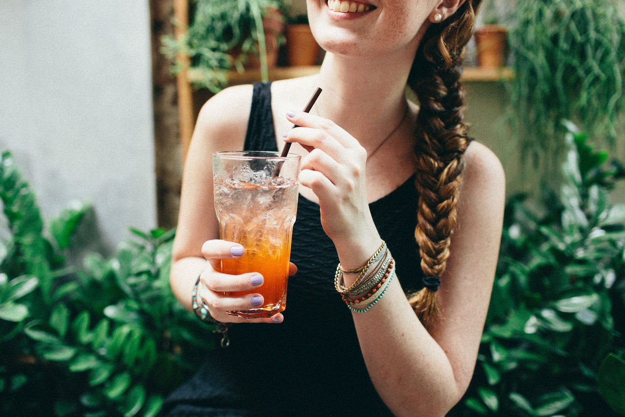 Midsection Of Cheerful Woman Having Cocktail By Plants