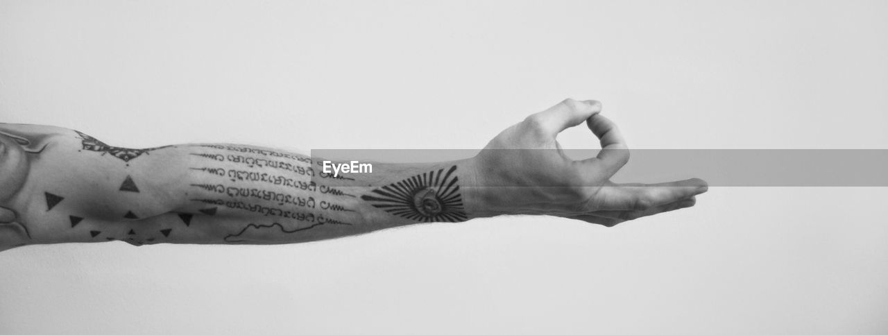 Cropped image of hand with tattoo gesturing mudra against white background