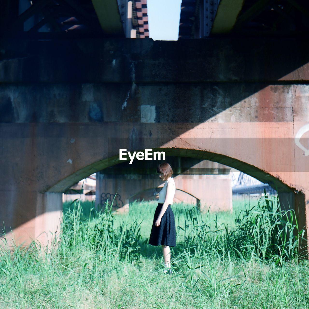 Side View Of Woman Standing Under Bridge