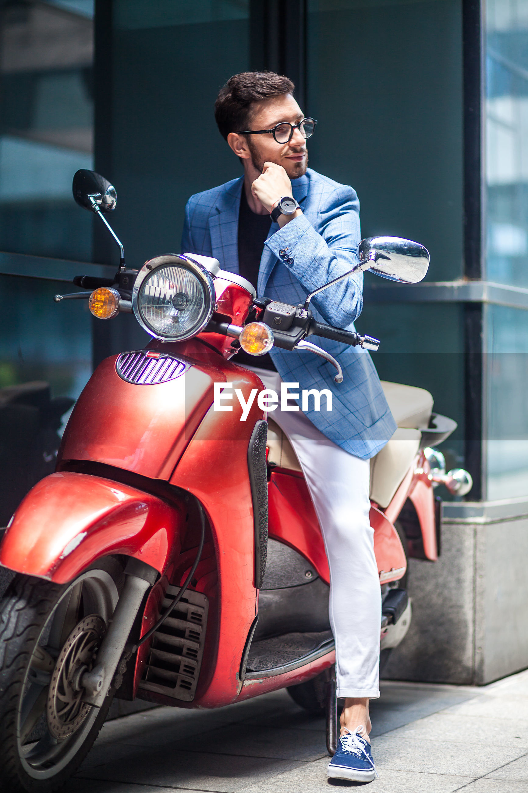Young businessman looking away while sitting on motor scooter