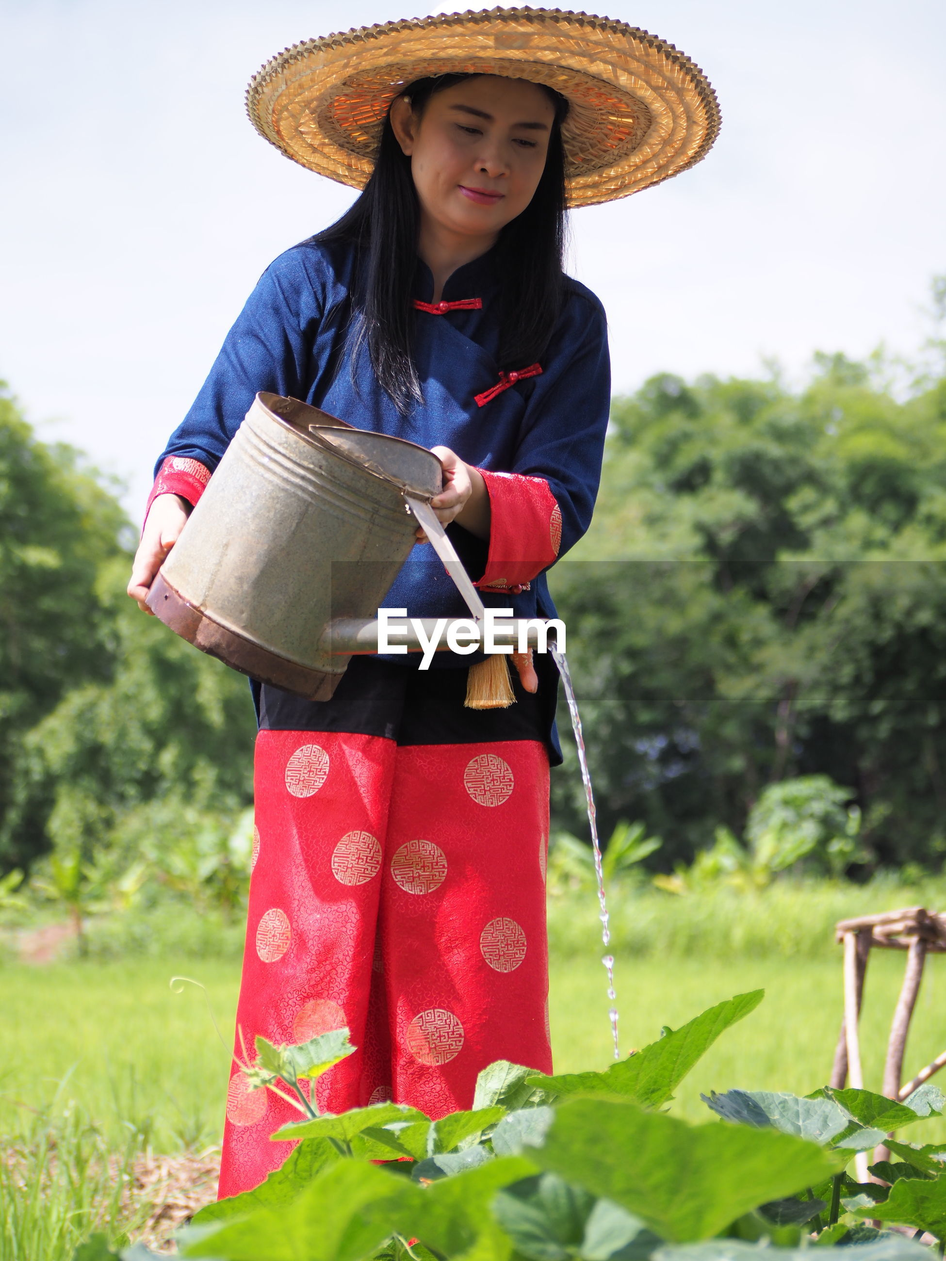 Woman watering plants while standing on agricultural field