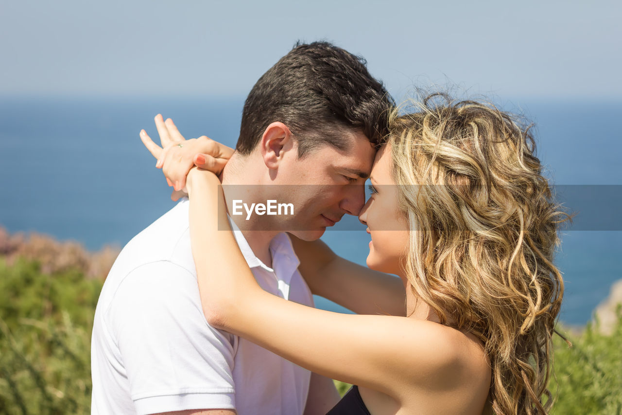 Close-up of couple embracing against sky