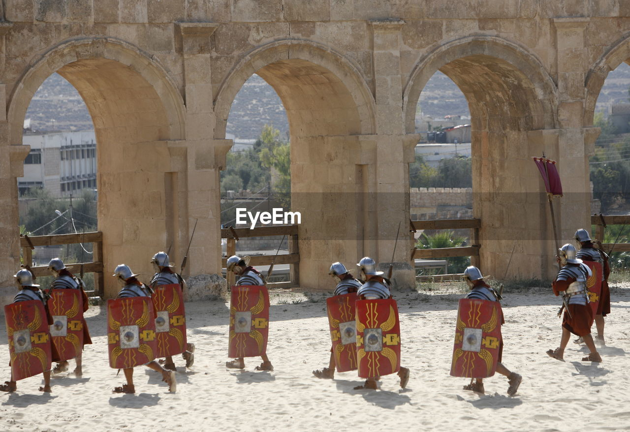 Soldiers with shield walking against arch built structure on battle field
