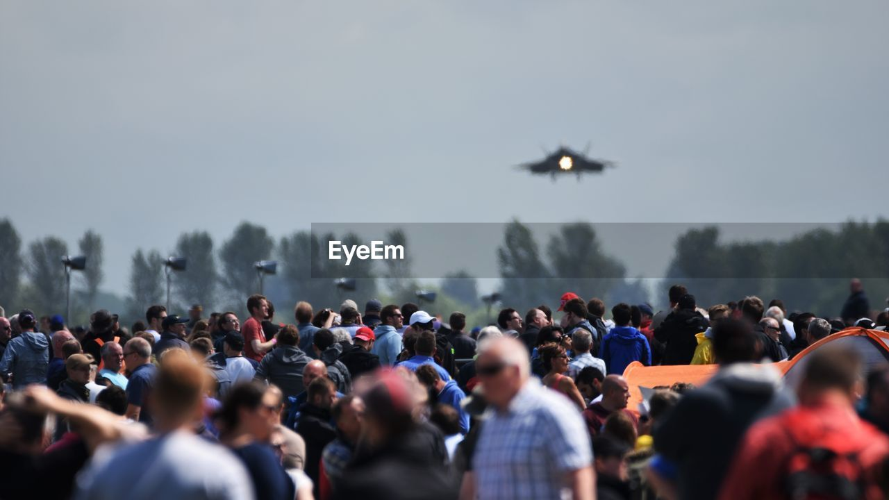 Crowd Watching Military Airplane Flying In Sky