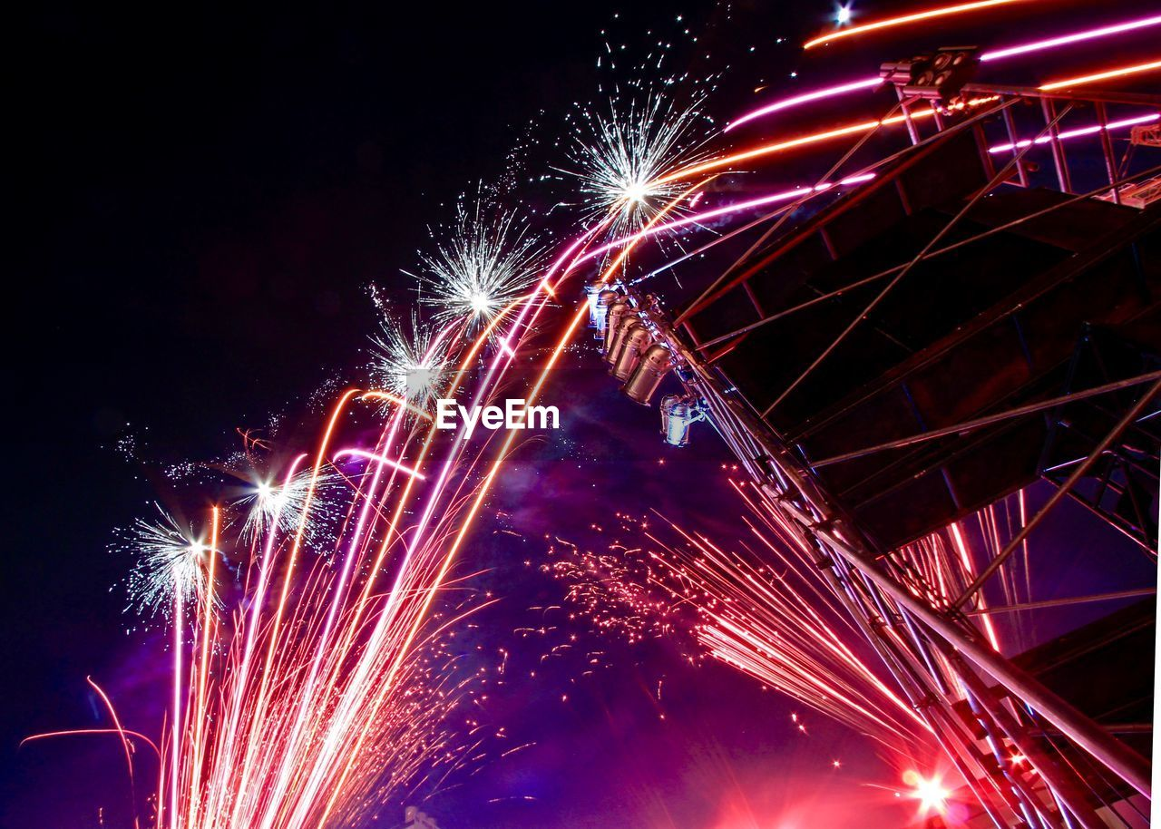 illuminated, motion, night, arts culture and entertainment, celebration, firework, long exposure, event, firework display, glowing, low angle view, exploding, blurred motion, sky, no people, nature, light, architecture, firework - man made object, multi colored, sparks, festival