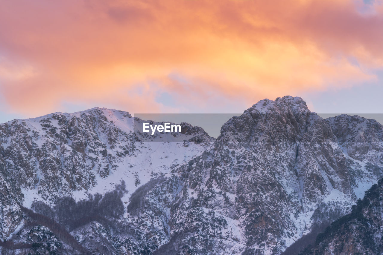 mountain, beauty in nature, nature, scenics, tranquility, sky, tranquil scene, snow, mountain range, cold temperature, winter, no people, outdoors, sunset, idyllic, cloud - sky, low angle view, physical geography, landscape, day