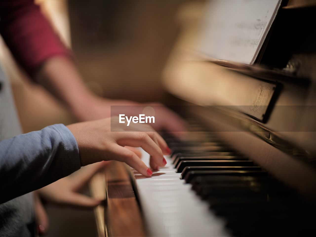 Cropped hand of woman playing piano at home
