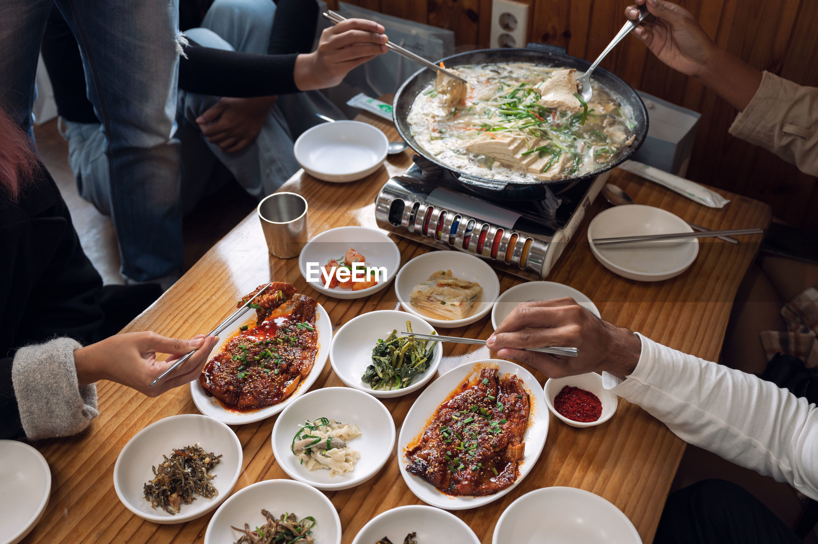 HIGH ANGLE VIEW OF PEOPLE HAVING FOOD IN RESTAURANT