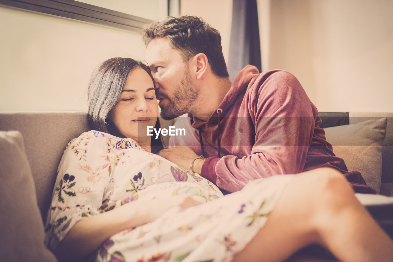 Man whispering in ear of pregnant woman at home