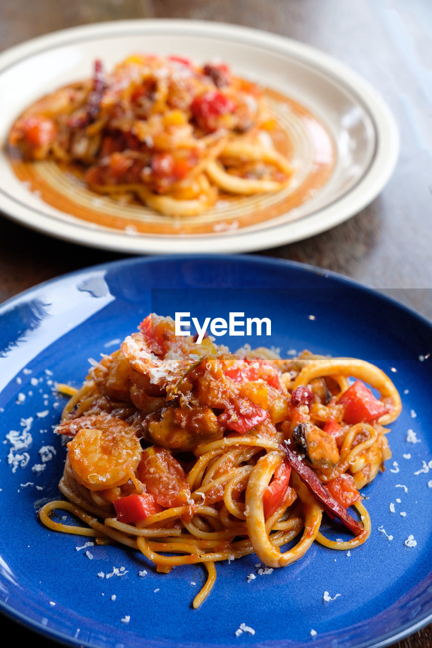 food, food and drink, ready-to-eat, plate, indoors, pasta, freshness, table, italian food, serving size, healthy eating, close-up, wellbeing, no people, still life, meal, high angle view, spaghetti, indulgence, focus on foreground, temptation, garnish, crockery, tomato sauce, dinner