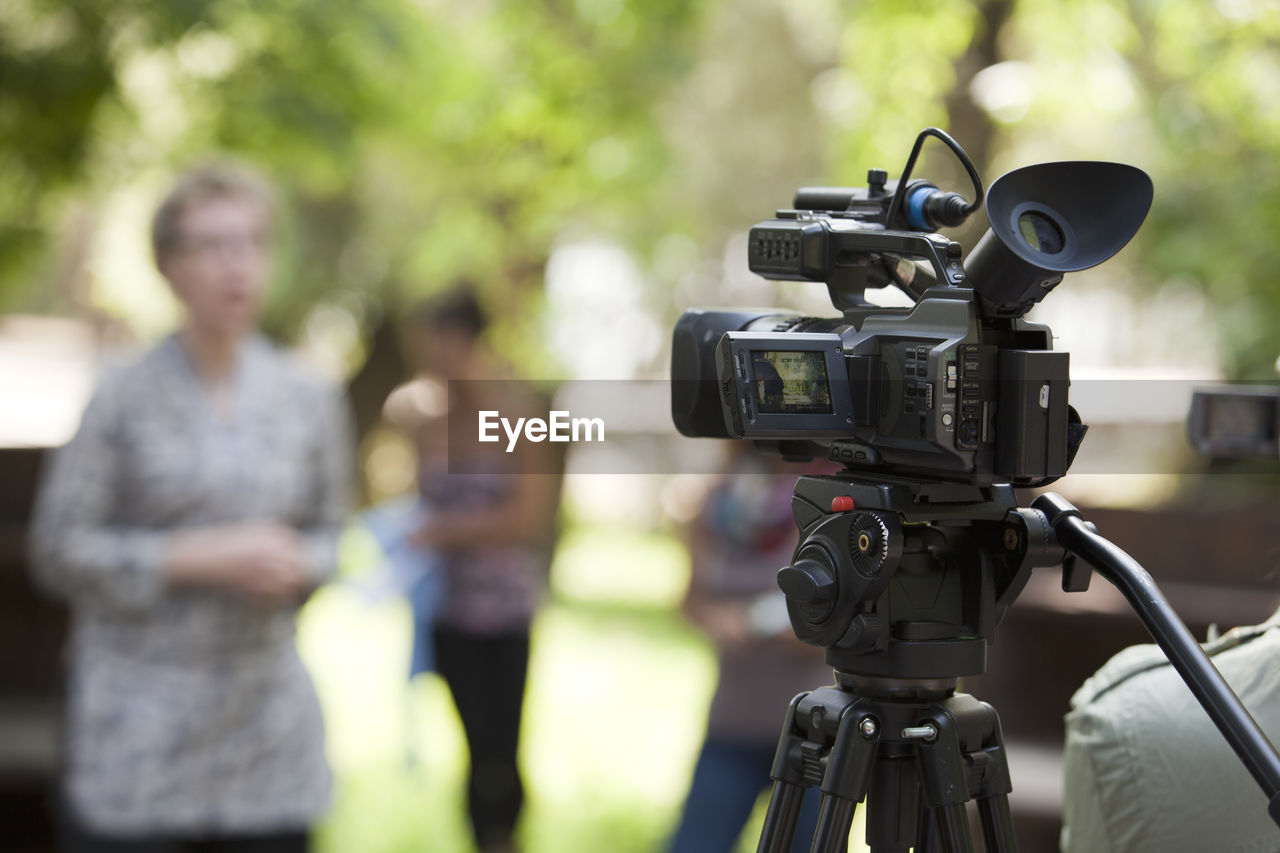 Close-up of television camera against people at park