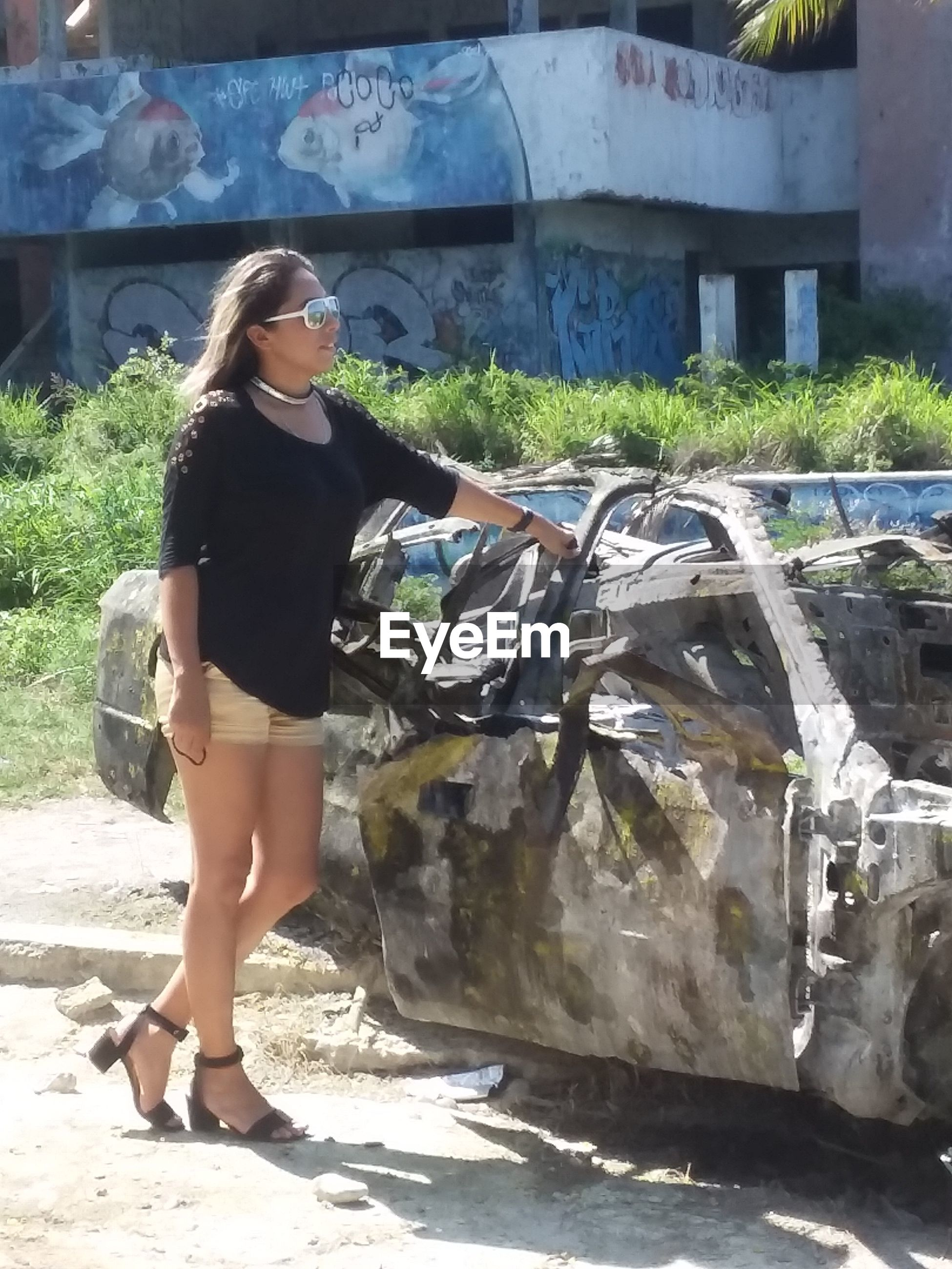 Full length of young woman standing by abandoned car
