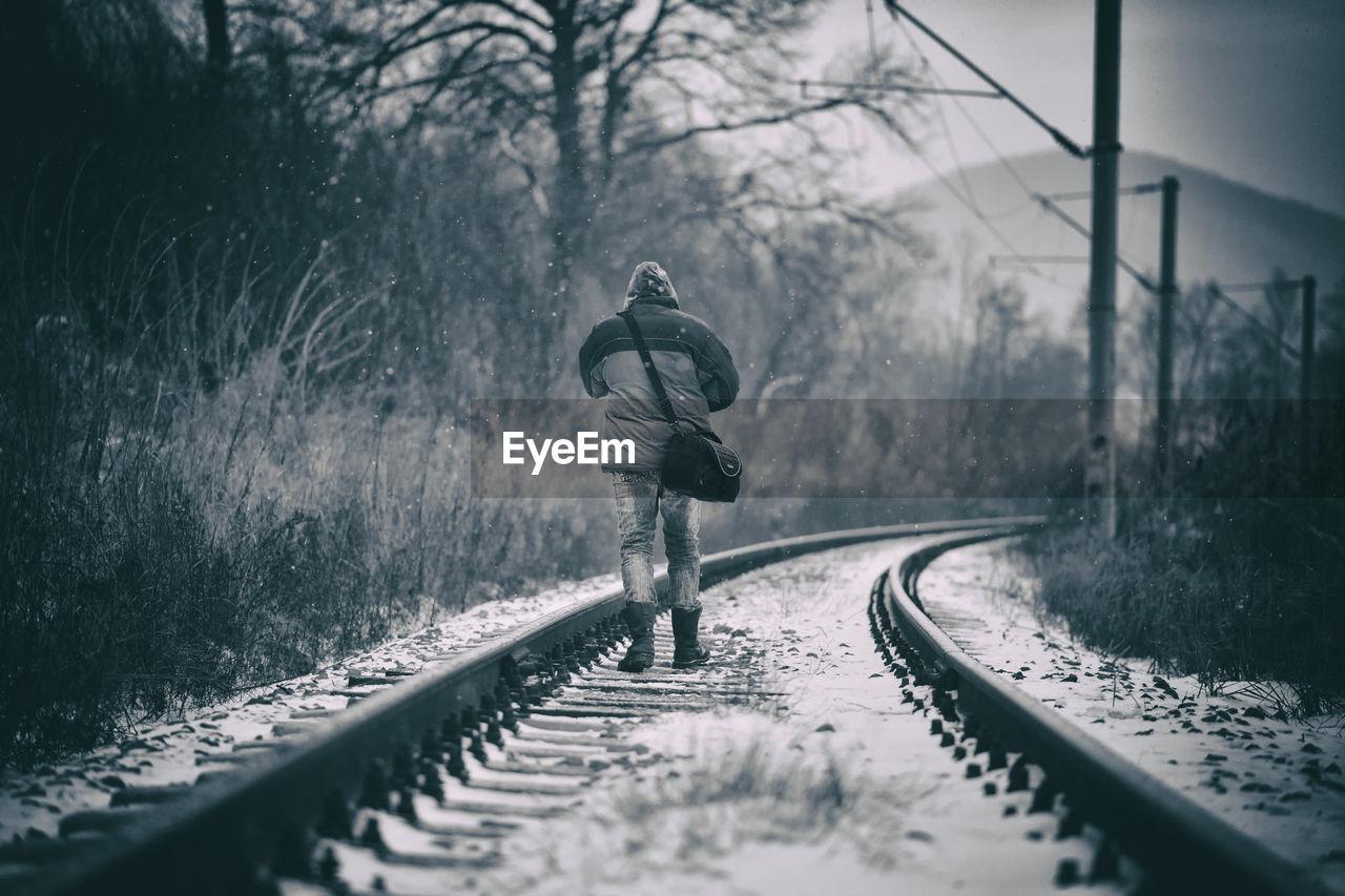 Rear View Of Man Walking On Railroad Track In Winter