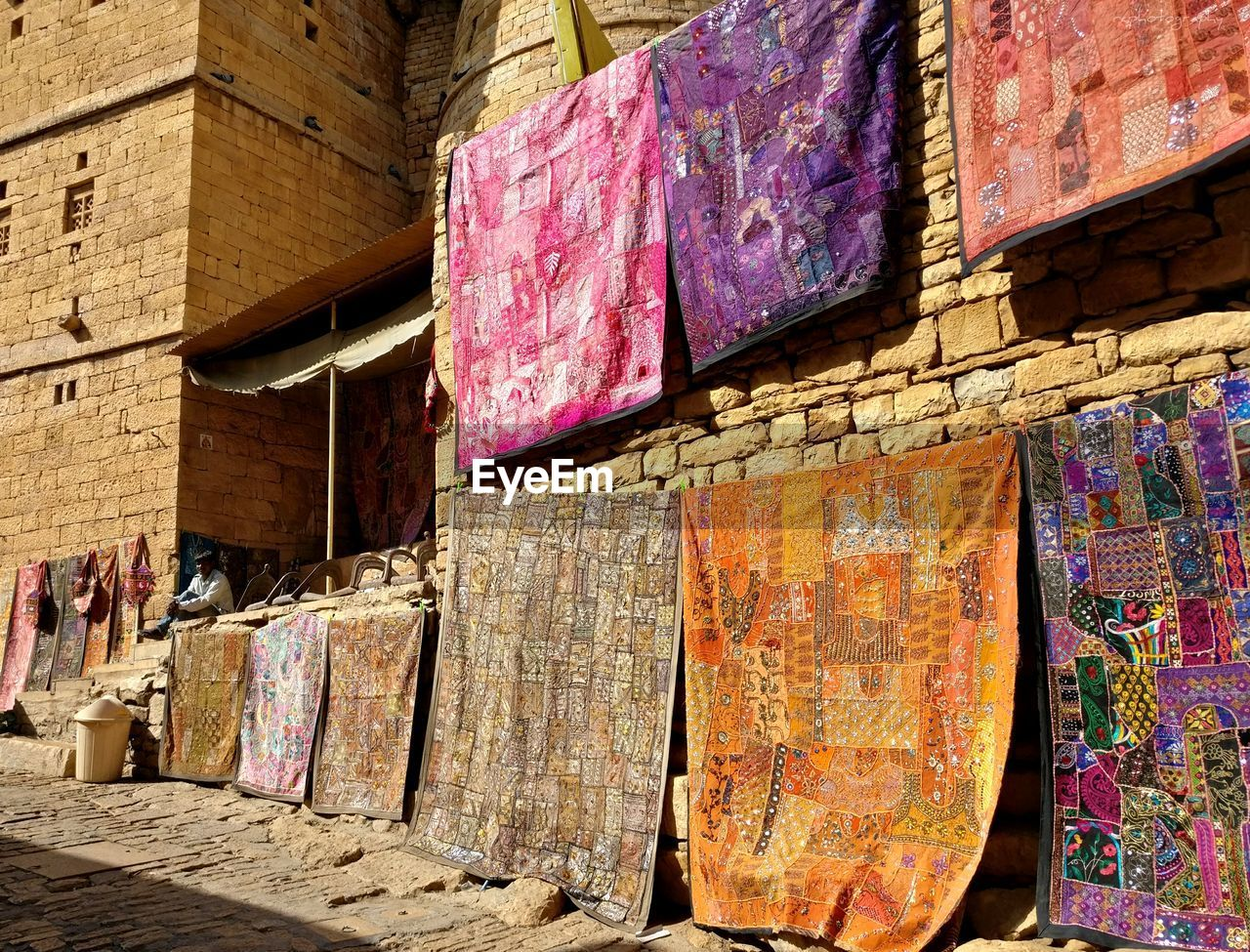 multi colored, no people, architecture, day, built structure, wall - building feature, wall, low angle view, outdoors, hanging, wood - material, building exterior, textile, large group of objects, variation, sunlight, pattern, industry, business, close-up
