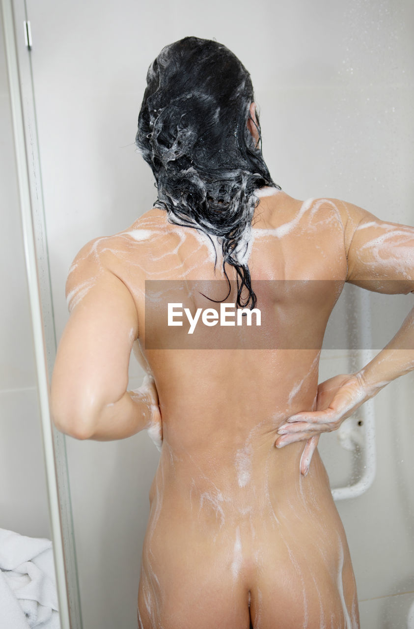 Rear view of naked woman bathing in bathroom