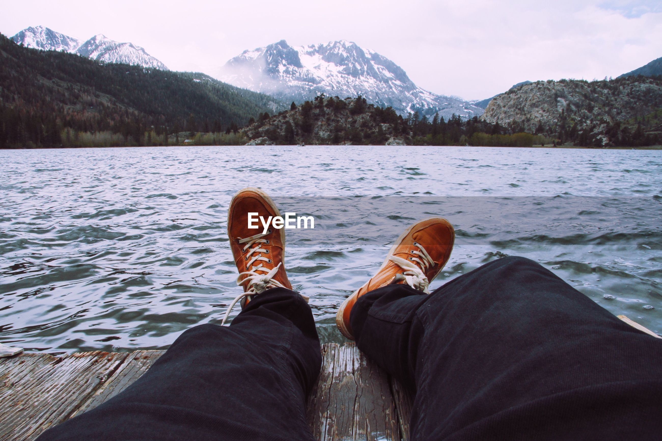 Low Section Of Man Sitting On Pier Against Lake