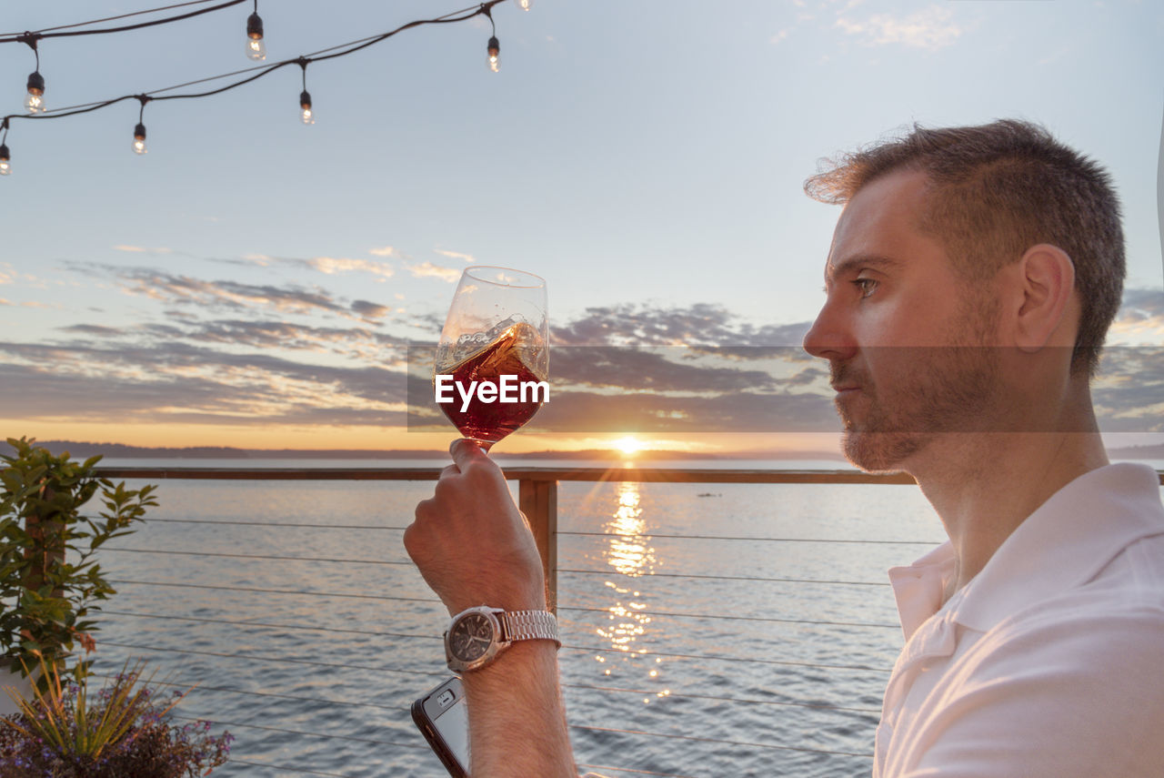 Profile View Of Mature Man Having Wine Against Sea During Sunset
