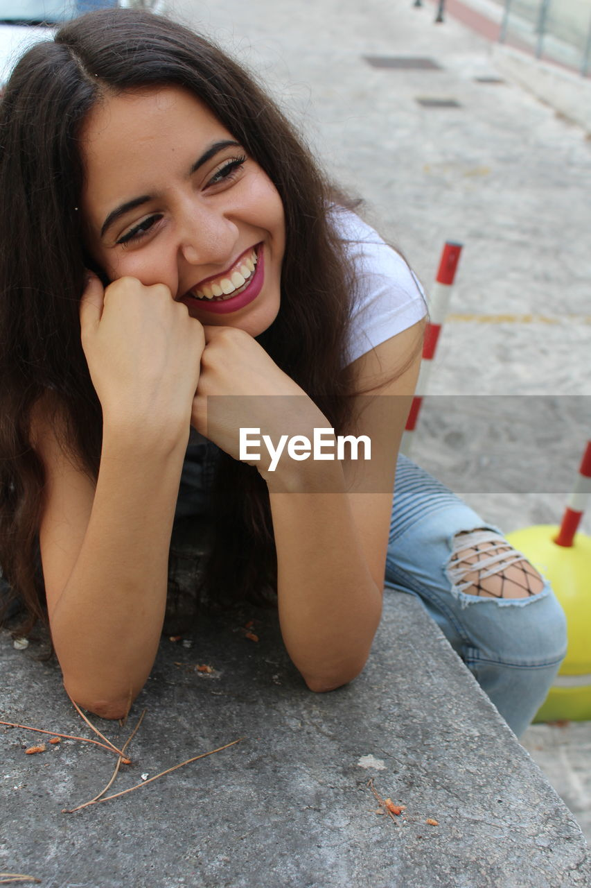 High Angle View Of Smiling Young Woman Looking Away In City
