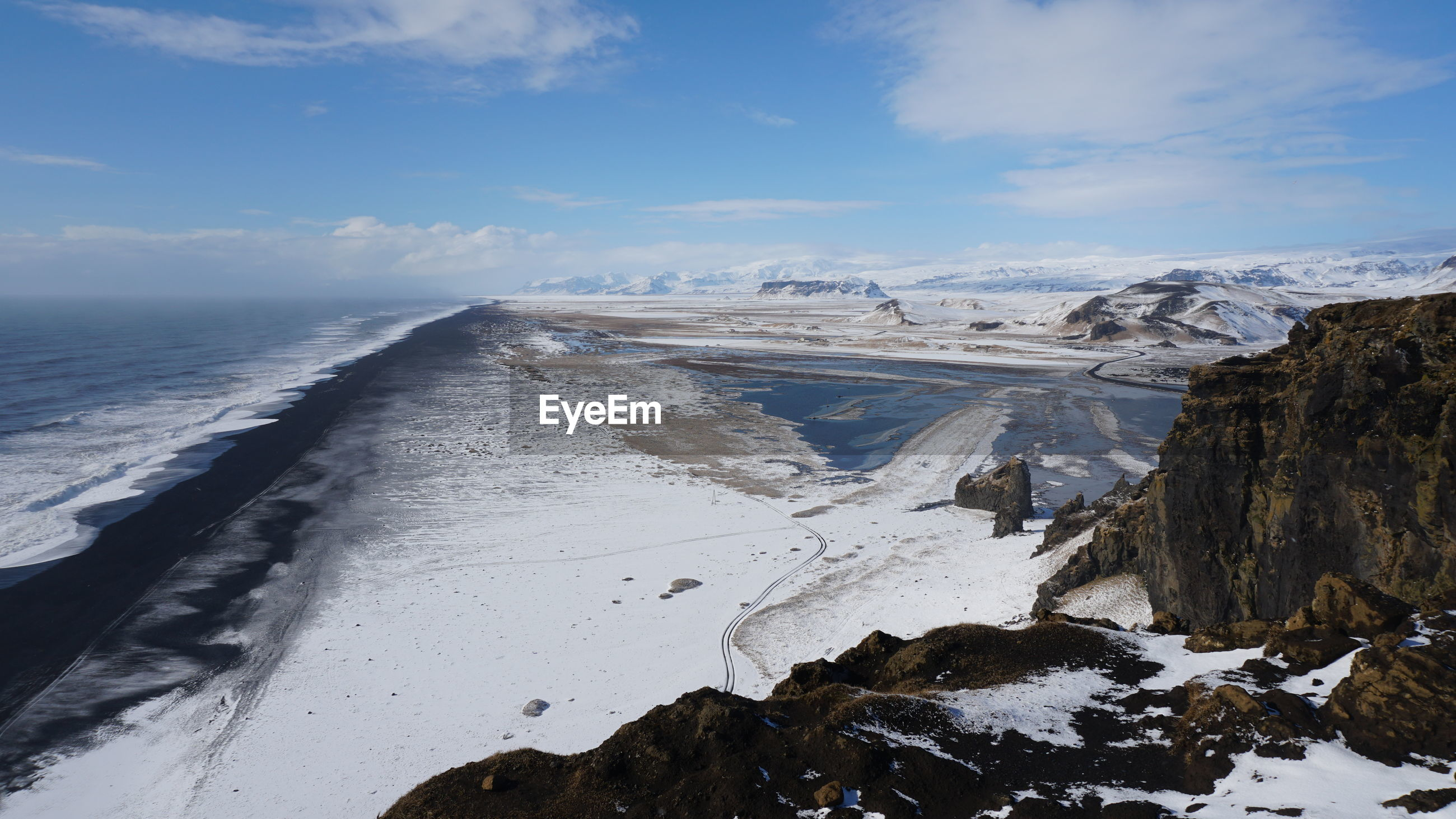 SCENIC VIEW OF SEA BY SNOWCAPPED MOUNTAIN AGAINST SKY