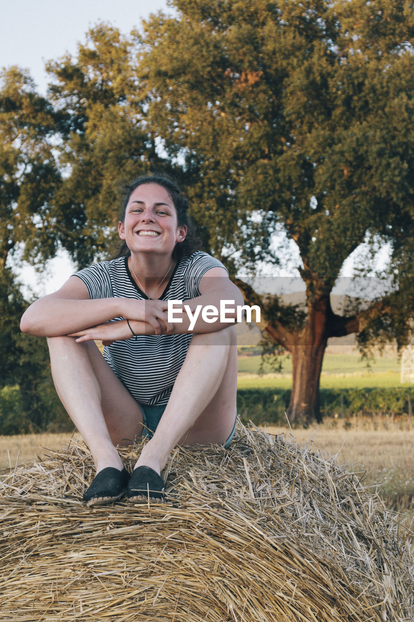 Young woman smiling wide atop a bale of hay on a farm