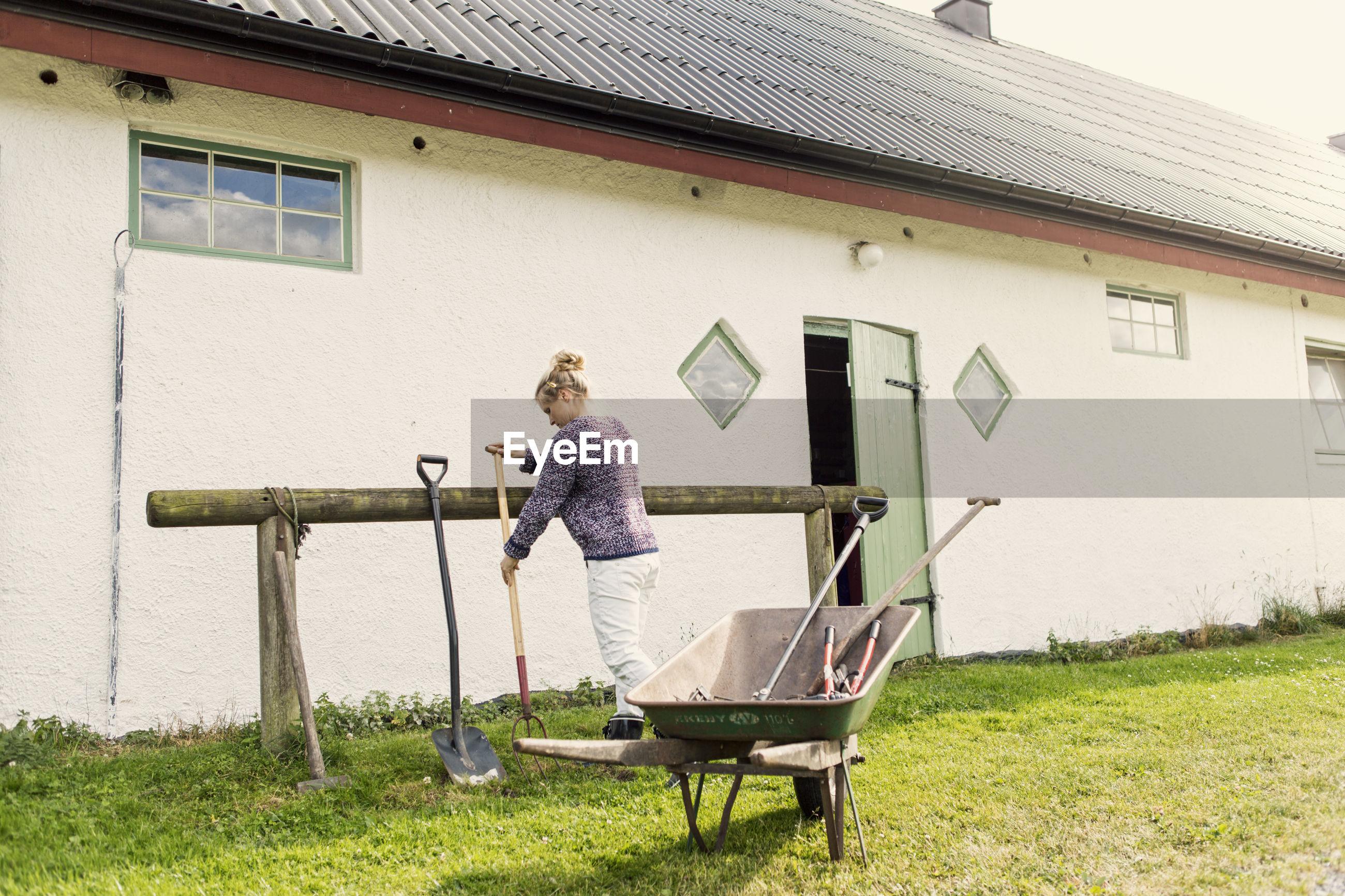 FULL LENGTH OF WOMAN STANDING OUTSIDE HOUSE