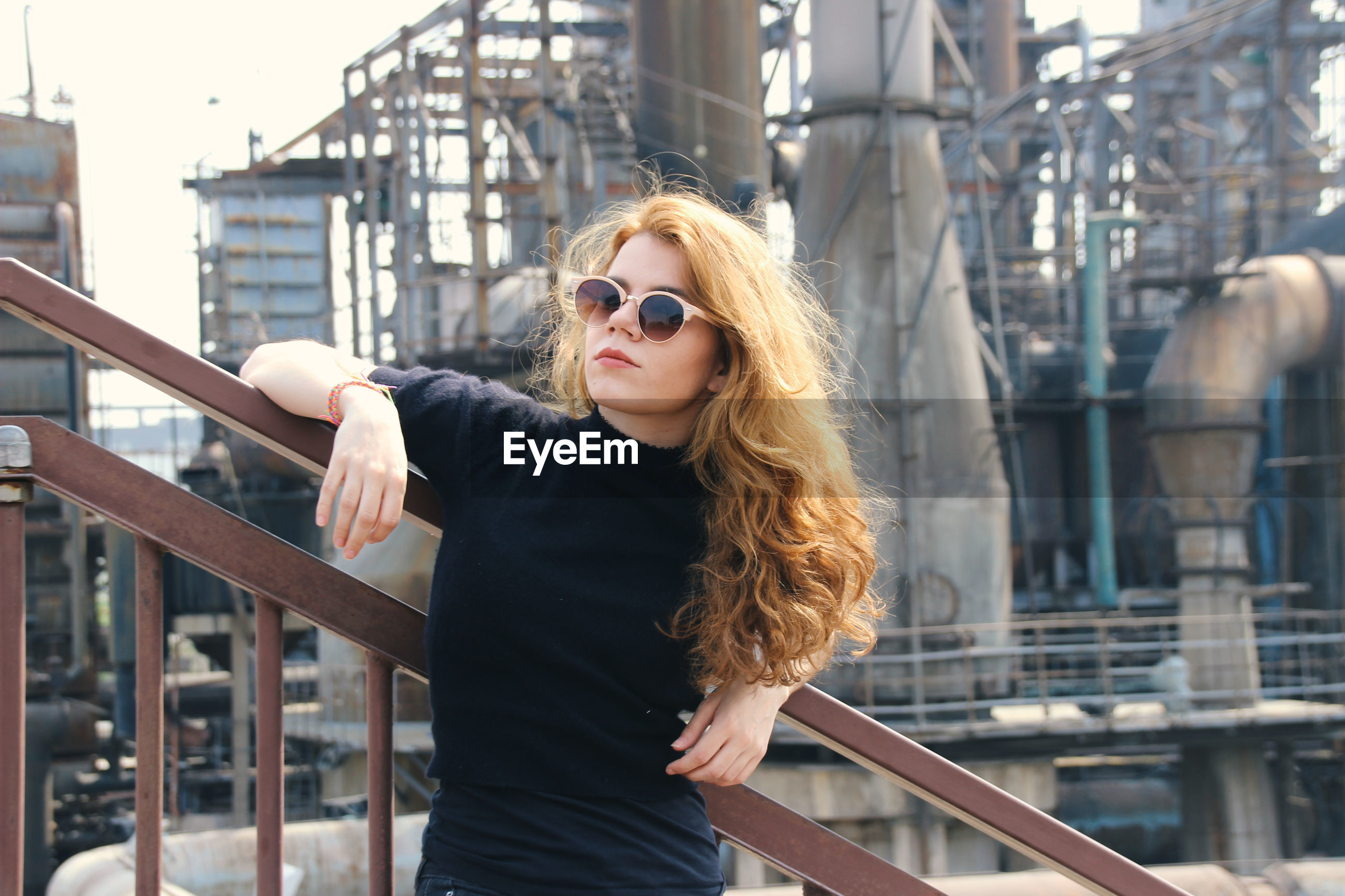 Woman in sunglasses standing against industry