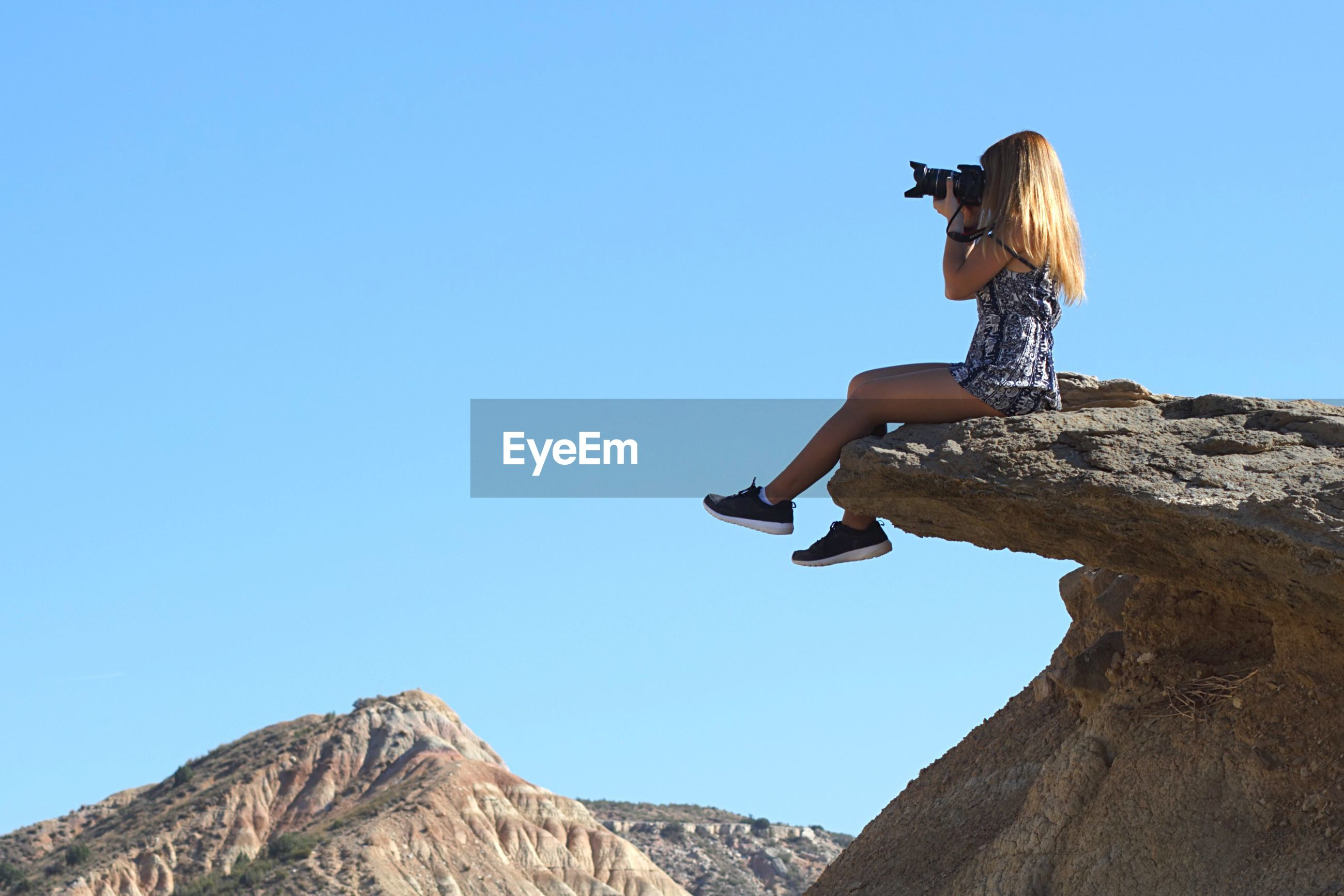 Low angle view of woman photographing while sitting on rock against clear blue sky