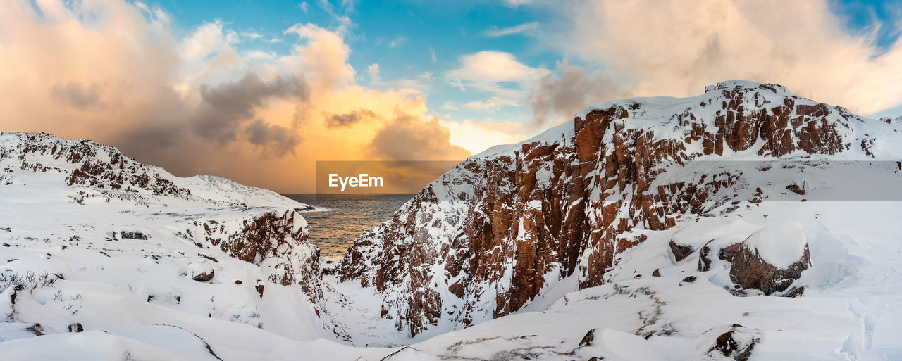 winter, sky, snow, cold temperature, beauty in nature, scenics - nature, cloud - sky, tranquility, tranquil scene, sunset, nature, non-urban scene, white color, no people, idyllic, covering, water, outdoors, environment, snowcapped mountain, extreme weather
