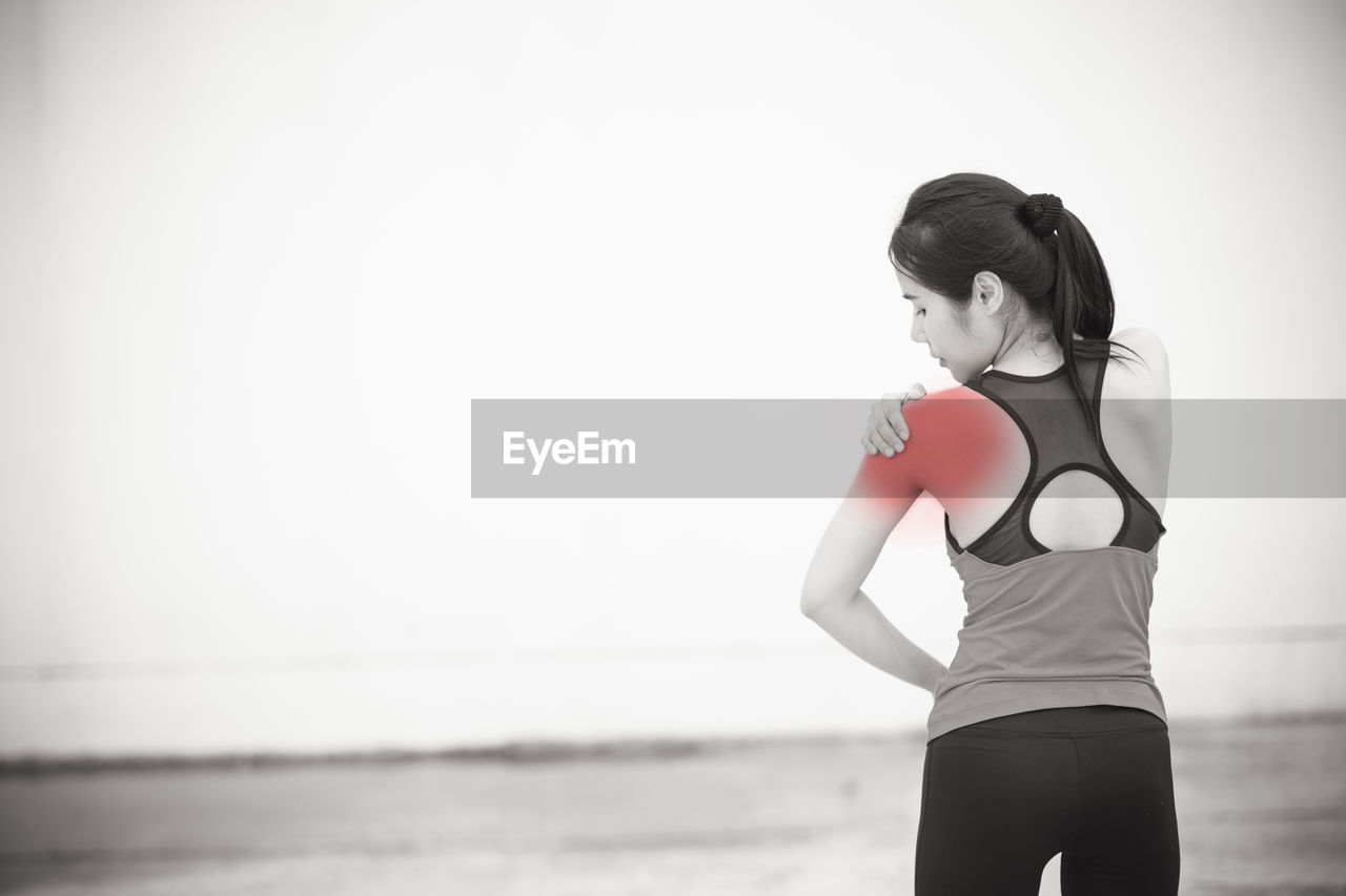 Rear view of woman with shoulder pain standing against wall