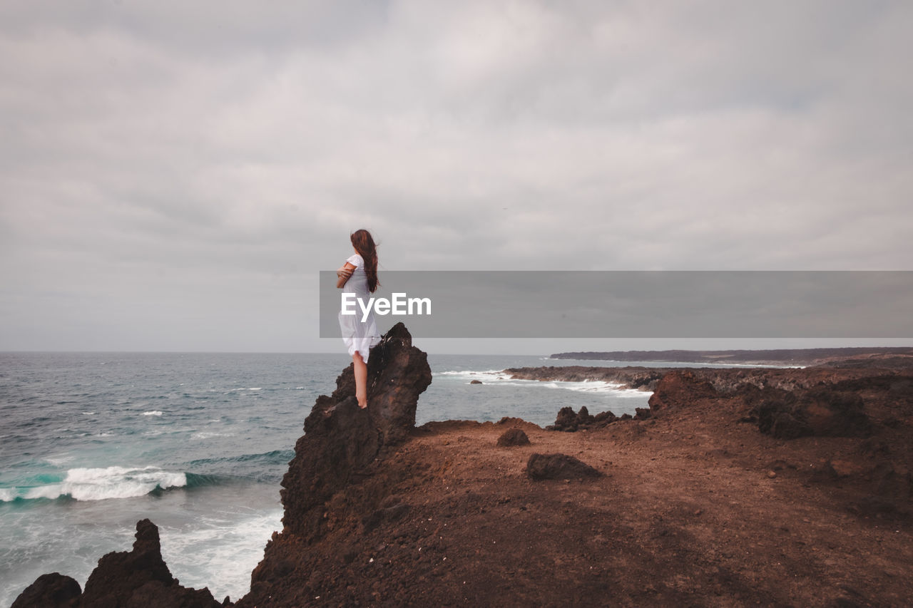 Woman standing on rock at beach against sky