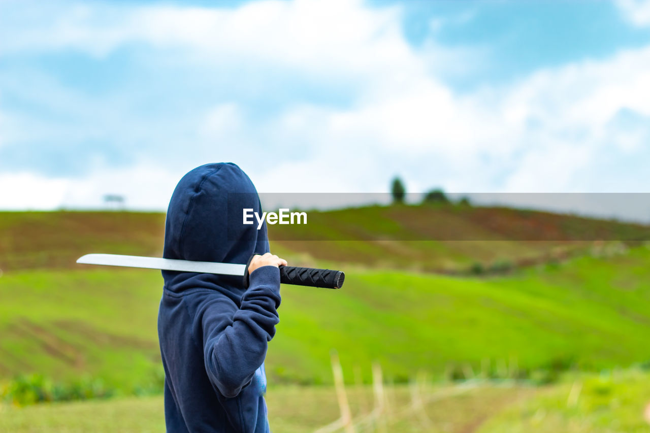 Boy in hooded shirt with sword on field