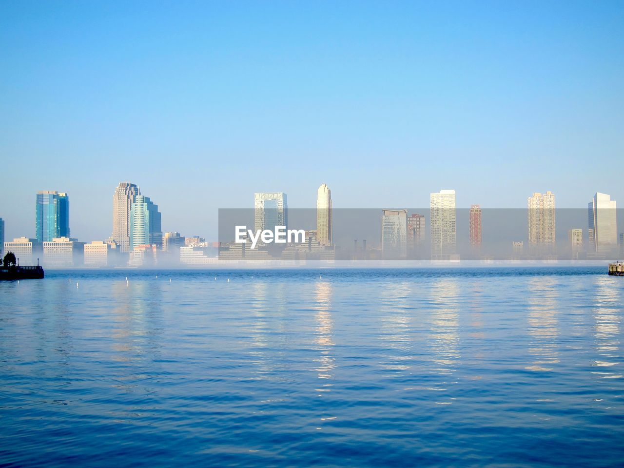 City Buildings By River Against Clear Sky