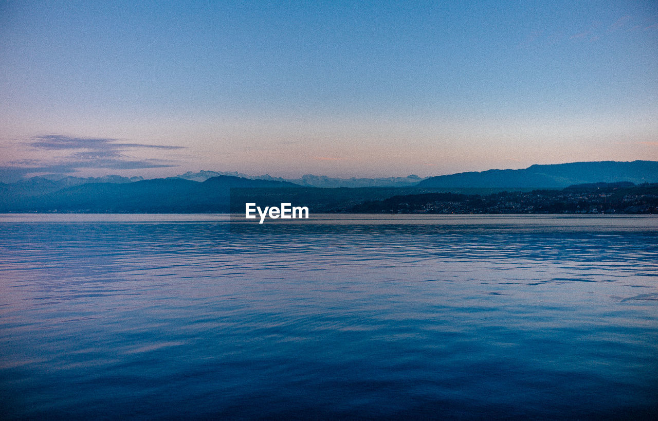 scenics, tranquil scene, beauty in nature, tranquility, nature, mountain, blue, water, no people, outdoors, sunset, idyllic, lake, mountain range, waterfront, sky, clear sky, day, view into land