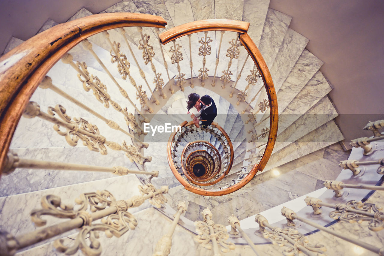 High Angle View Of Couple Standing On Spiral Stairs