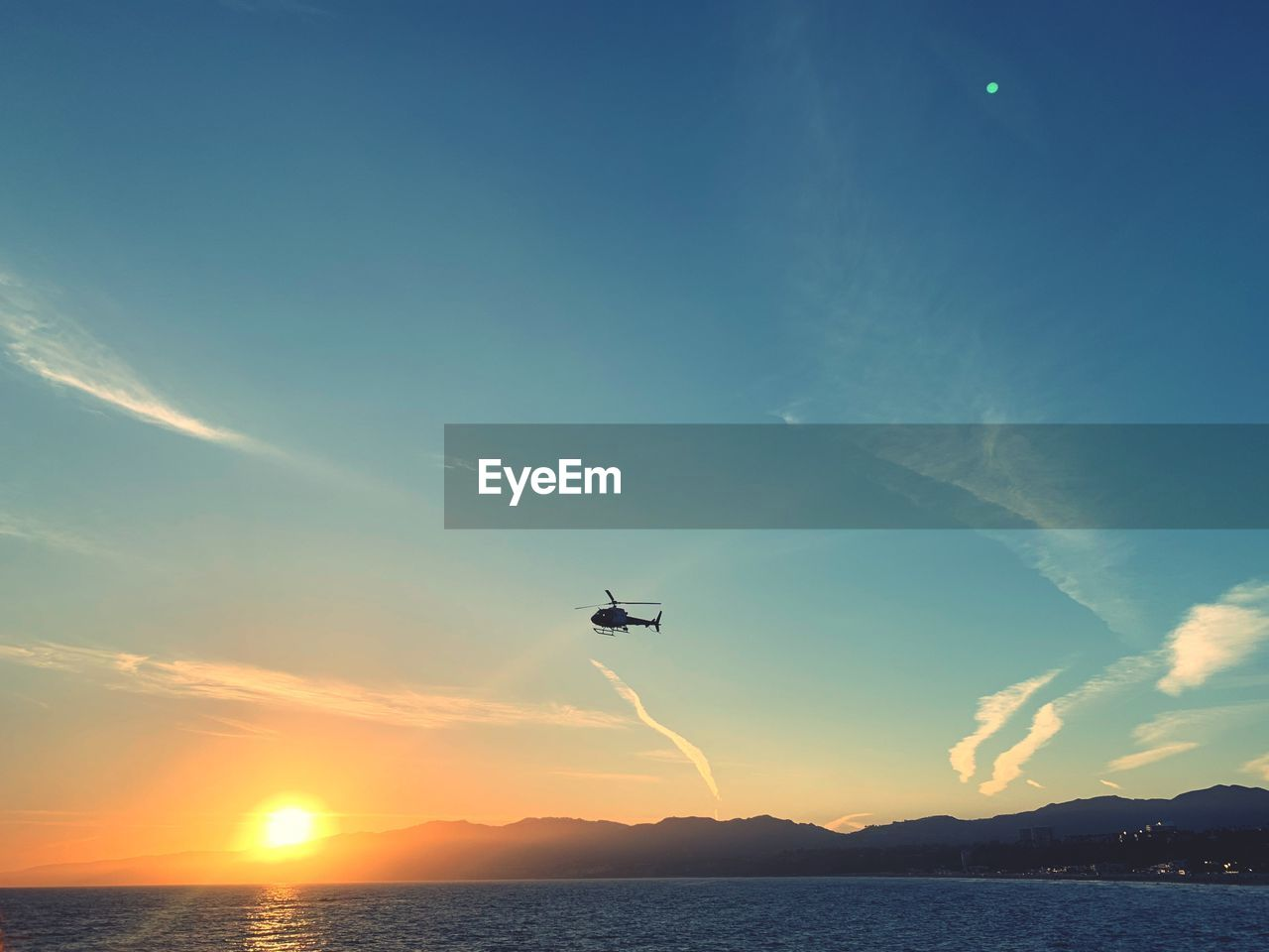 sky, flying, beauty in nature, scenics - nature, water, nature, sea, mid-air, cloud - sky, tranquility, sunset, tranquil scene, mountain, non-urban scene, mode of transportation, no people, air vehicle, sunlight, idyllic, outdoors