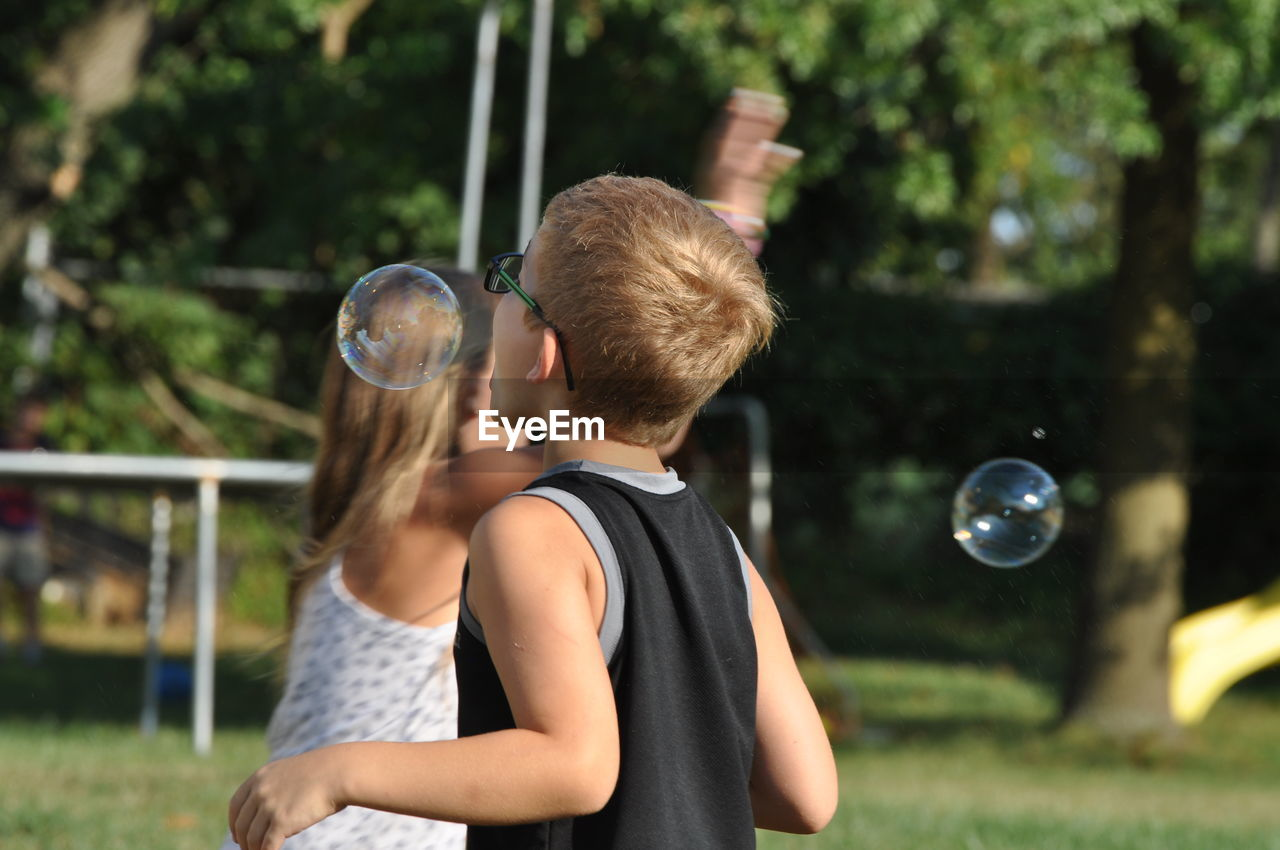 real people, focus on foreground, leisure activity, bubble, two people, bubble wand, childhood, fun, lifestyles, casual clothing, blond hair, rear view, day, boys, outdoors, togetherness, young adult, young women, nature, people