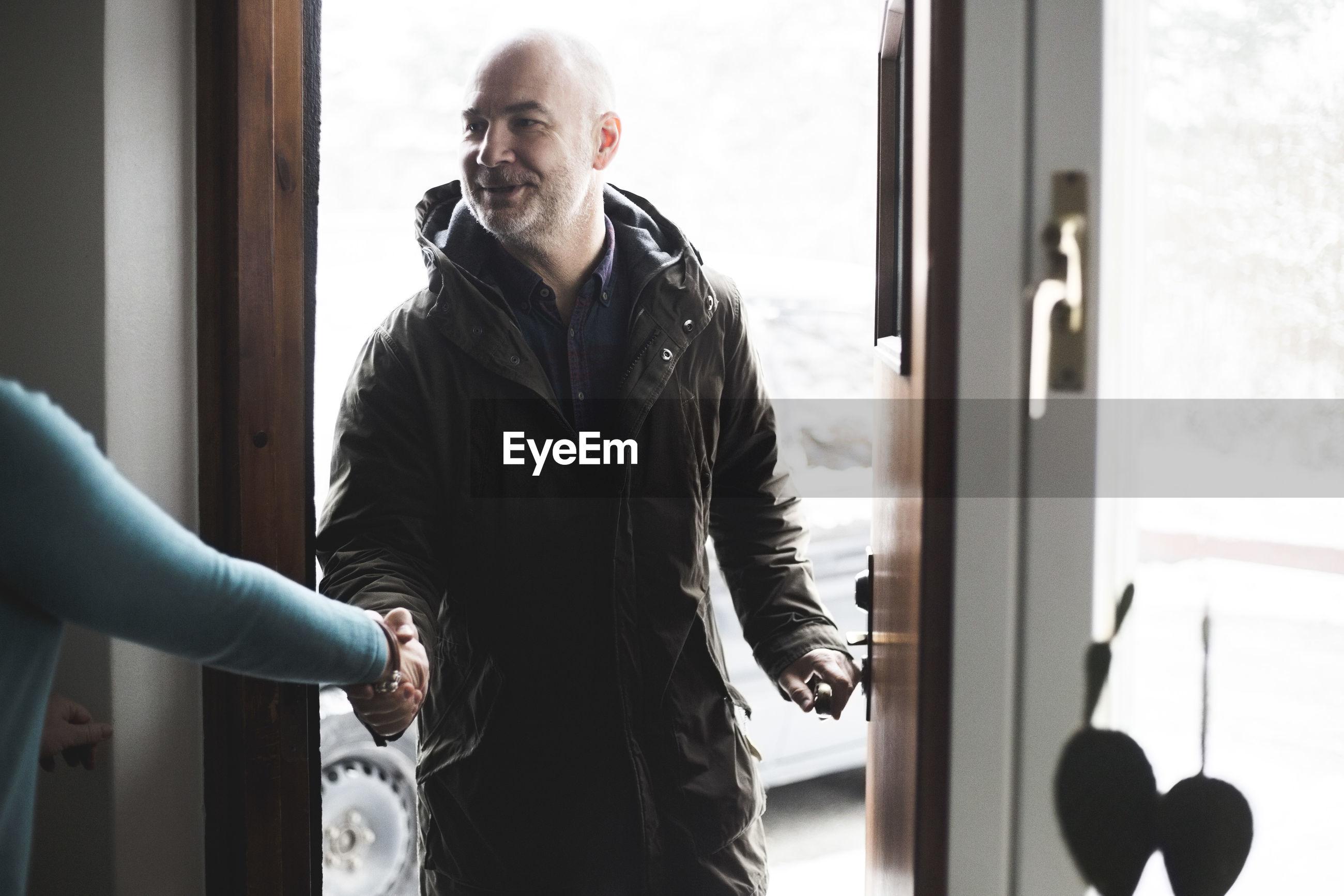 Mature man shaking hands with doctor at open doorway
