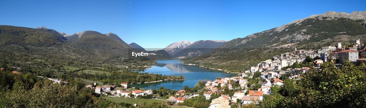 Panoramic View Of Lake And Buildings Against Clear Blue Sky