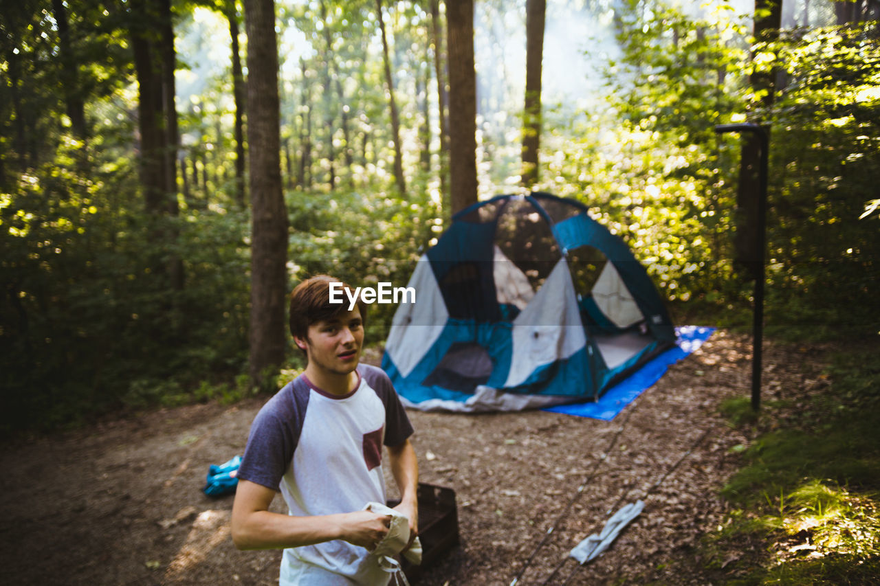 camping, forest, tent, tree, day, adventure, sitting, outdoors, nature, real people, young adult, people, adult