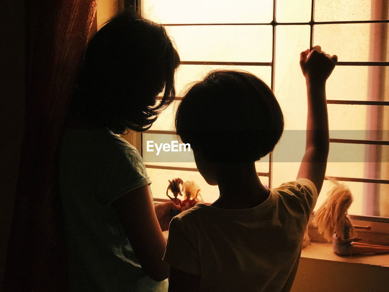Rear View Of Mature Woman With Daughter Standing By Window At Home