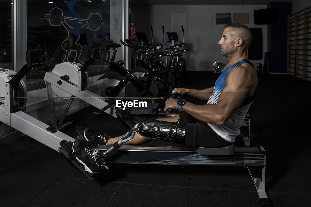 Side view of determined disabled man exercising on rowing machine at gym