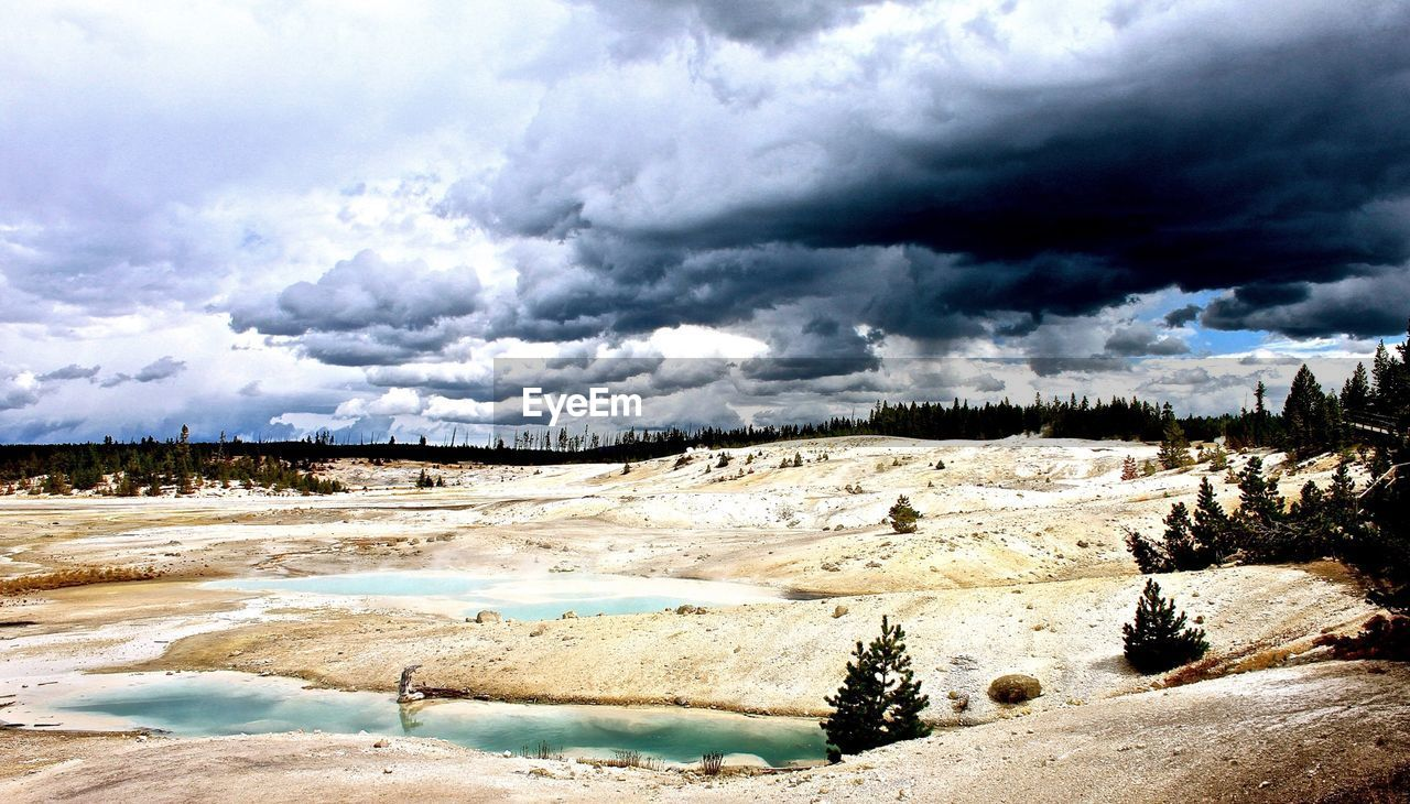 Scenic view of hot spring in yellowstone national park against cloudy sky