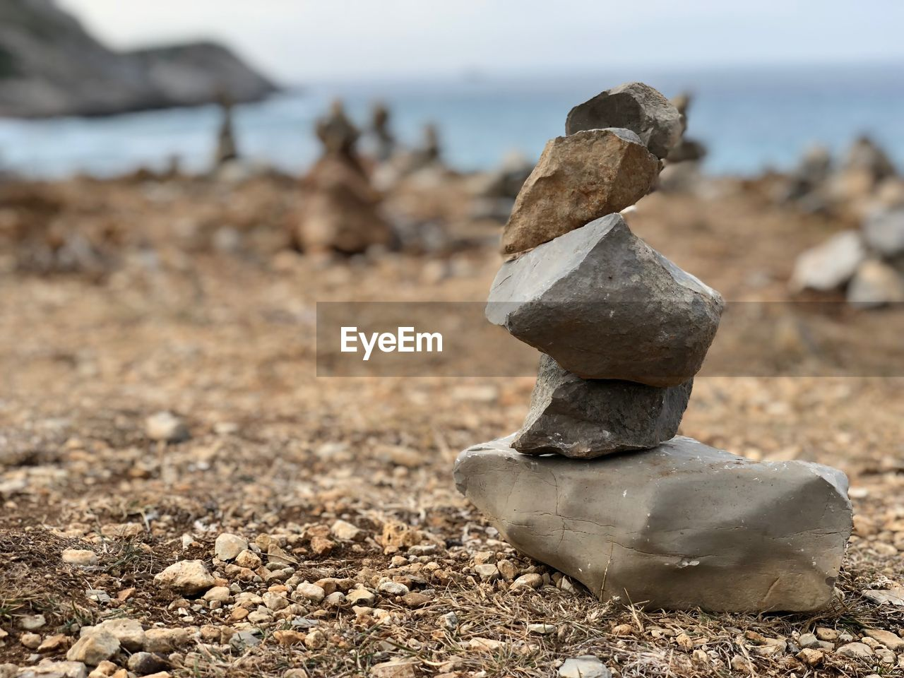 focus on foreground, no people, day, land, nature, close-up, solid, rock, outdoors, stack, beach, field, balance, rock - object, tranquility, sea, stone - object, water, sky, tranquil scene, pebble