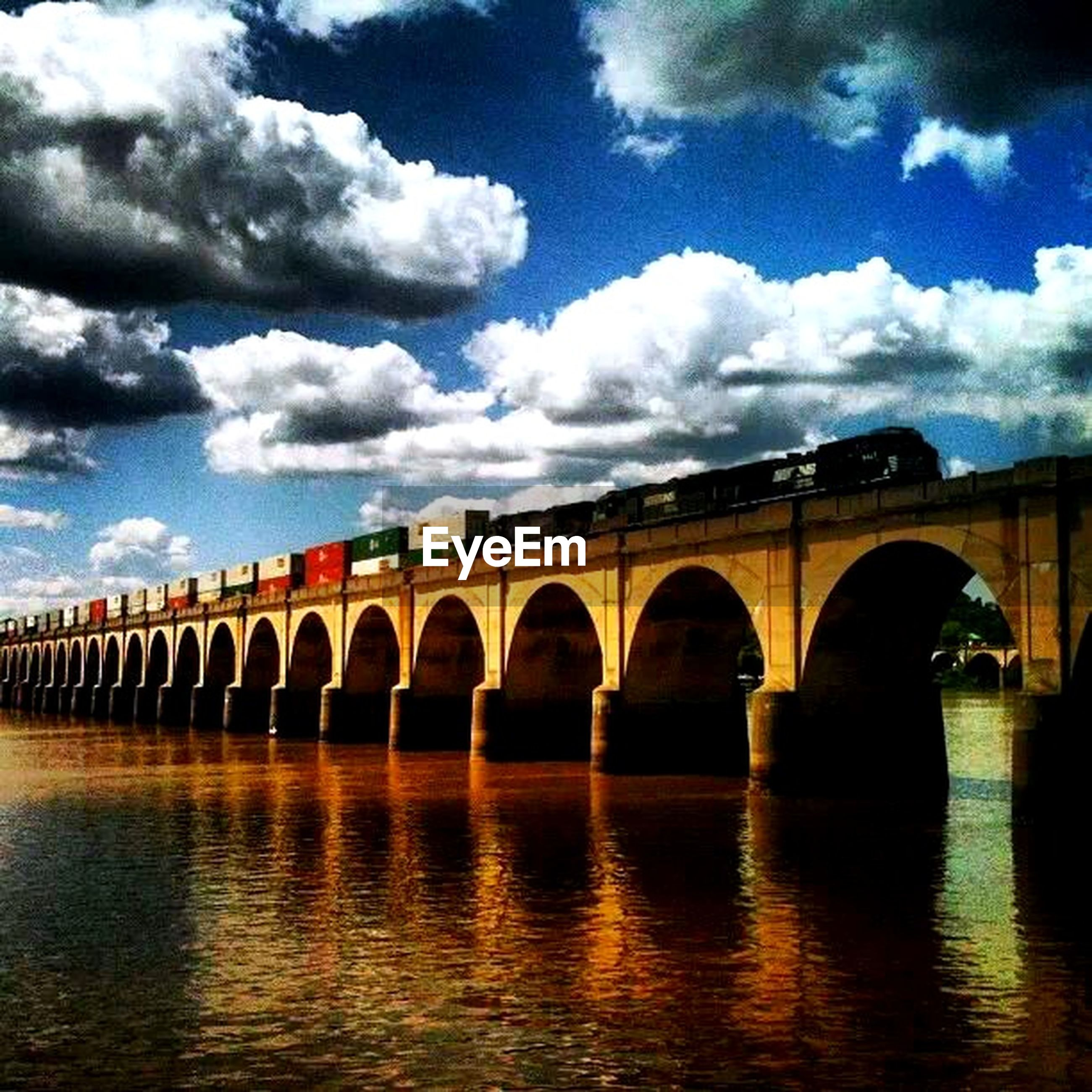 architecture, built structure, arch, connection, bridge - man made structure, sky, water, bridge, arch bridge, waterfront, river, cloud - sky, cloud, reflection, engineering, building exterior, transportation, outdoors, no people, day
