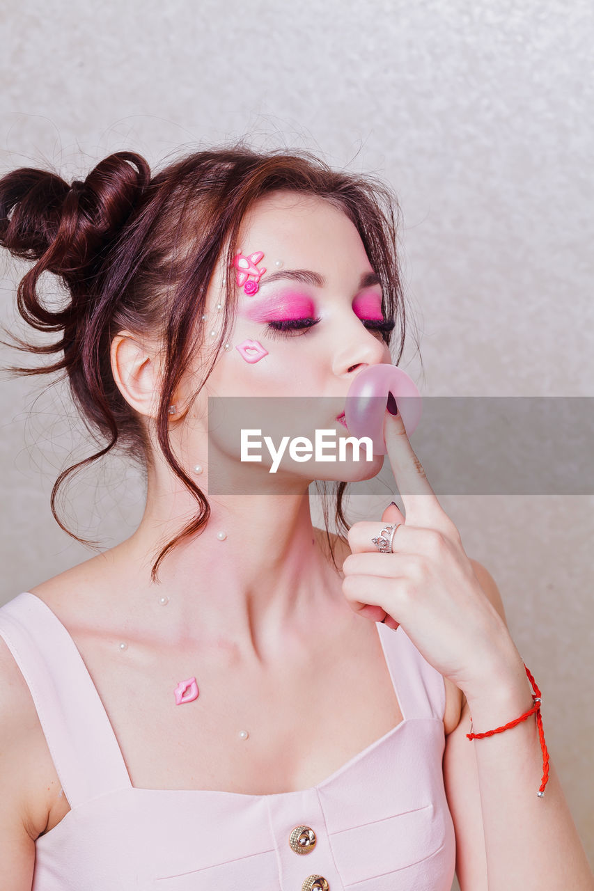 Close-up of beautiful woman with make-up blowing bubble gum against wall