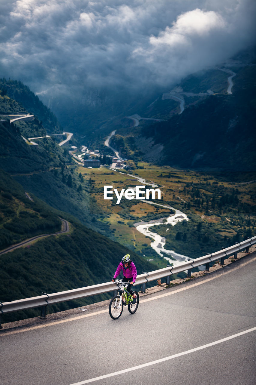 Woman Riding Bicycle On Mountain Road