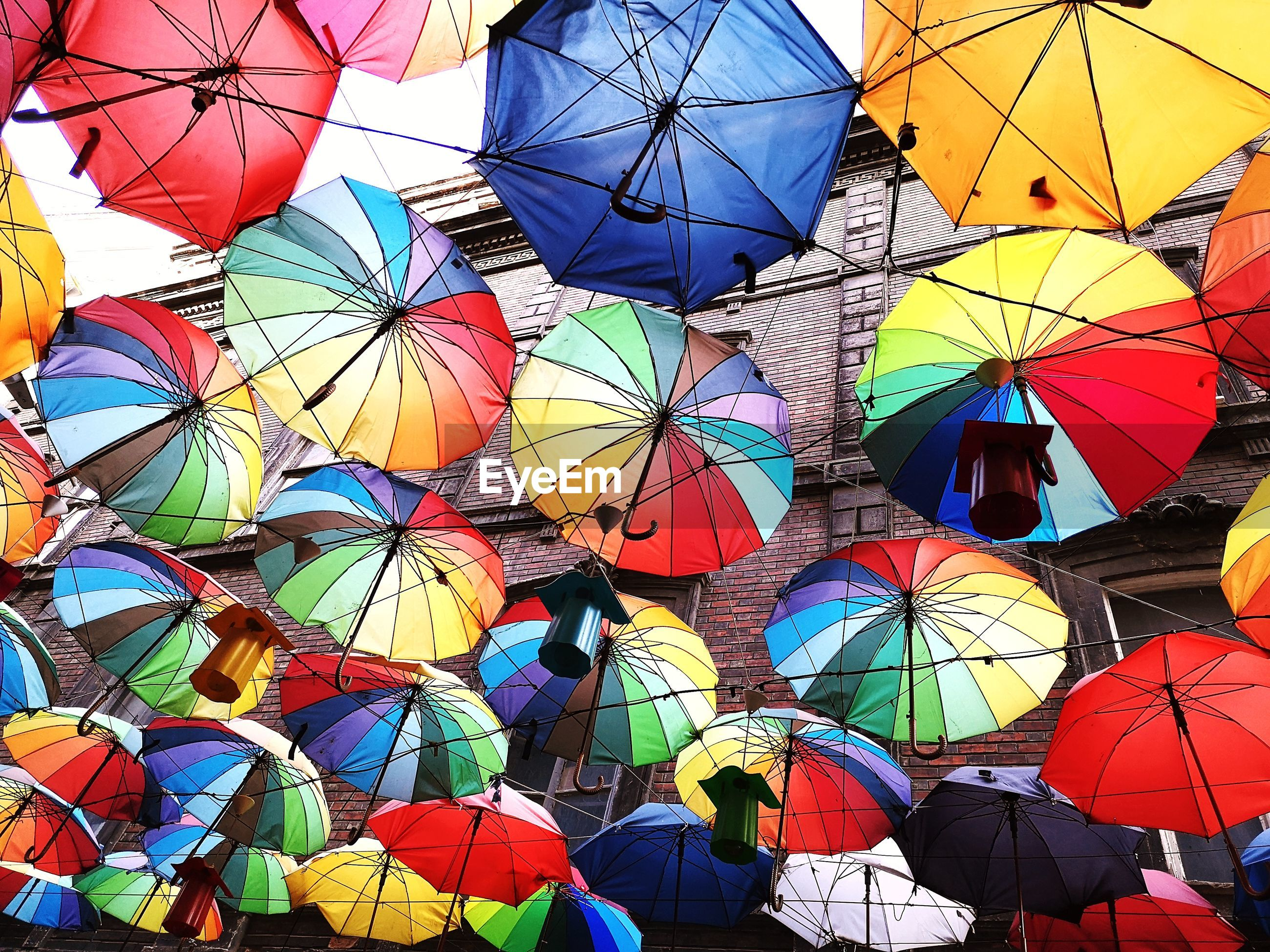 Low angle view of multi colored umbrellas at market stall