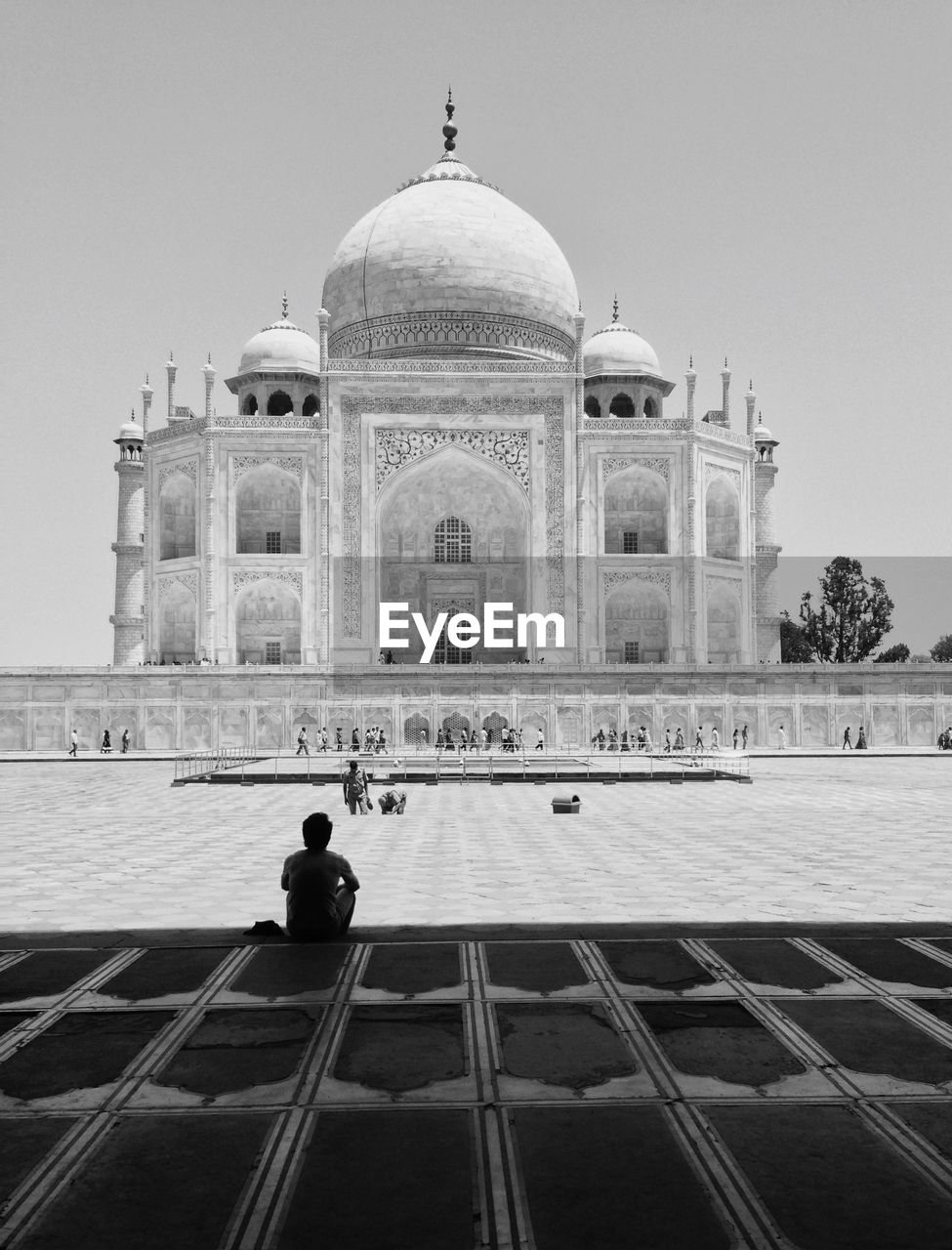 Rear View Of Man Sitting Against Taj Mahal In City