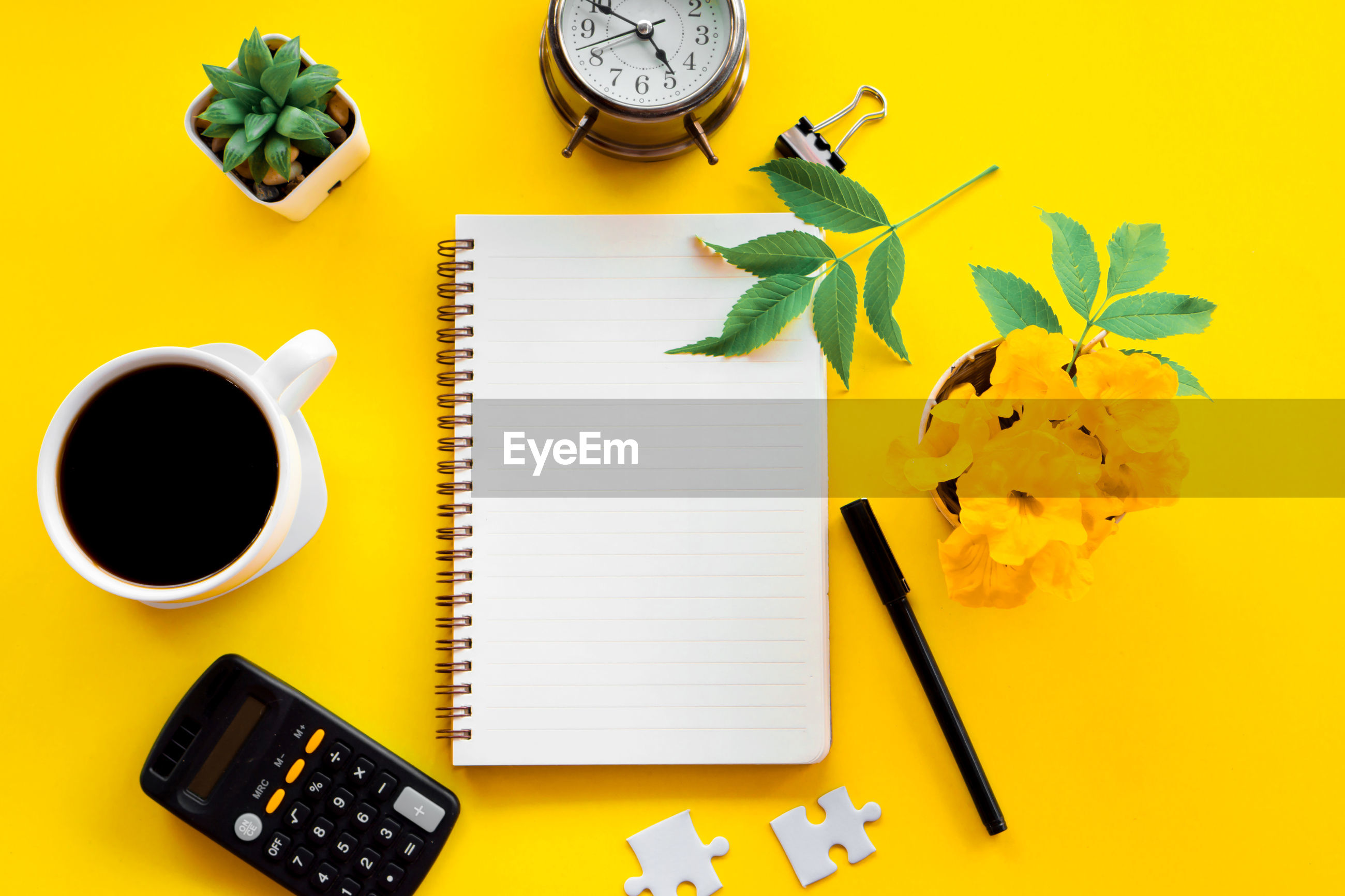 Business flat lay with notepad ,pen,coffee cup on yellow background